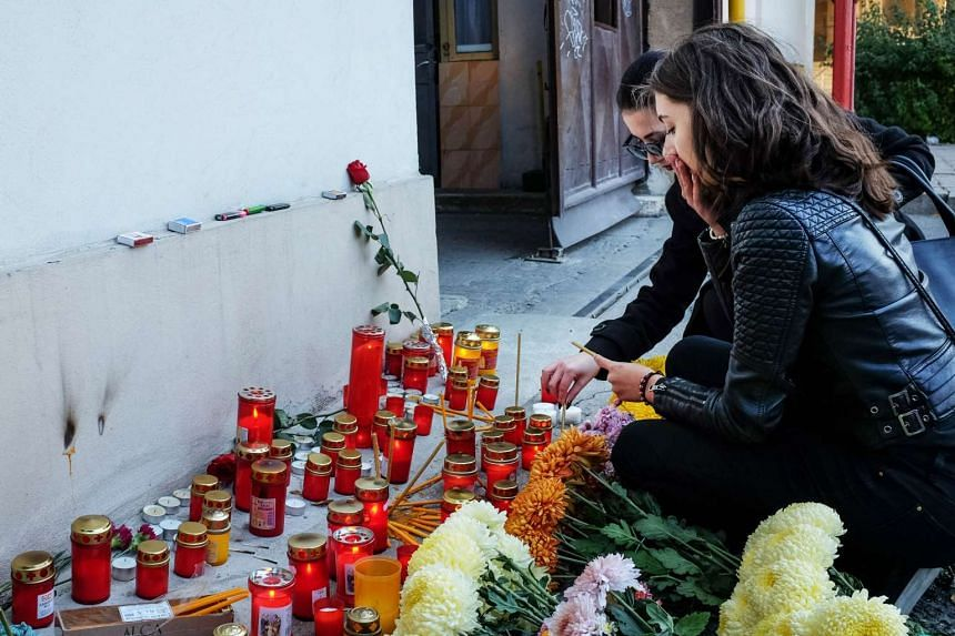 Women light candles in front of a club where a fire broke out, in Bucharest, Romania, on Oct 31. 2015.