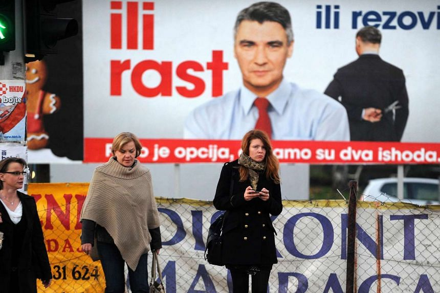 """People walking past an election campaign billboard for the """"Croatia forward"""" coalition led by Mr Zoran Milanovic, in downtown Zagreb, on Nov 6, 2015."""