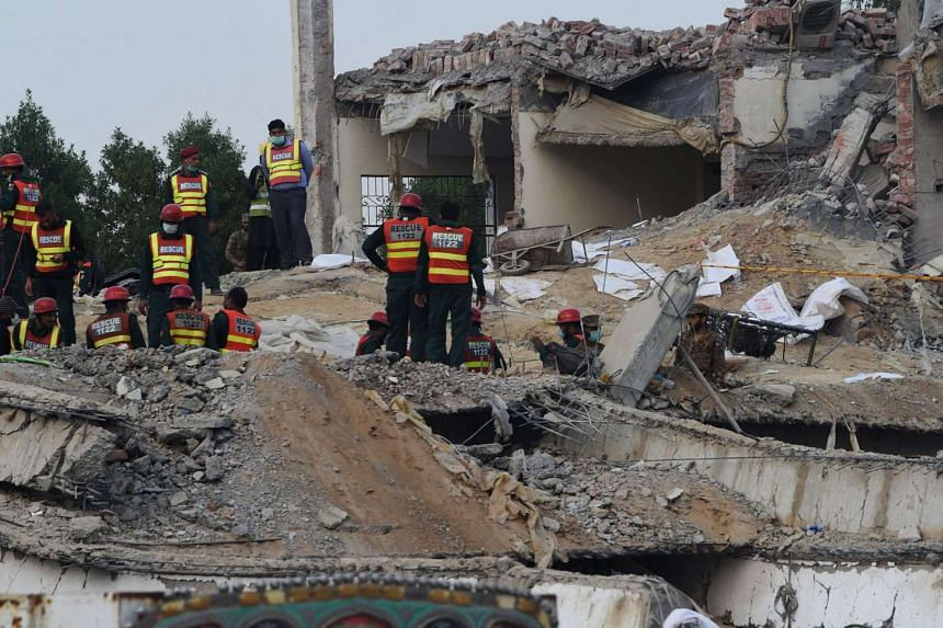 Pakistani rescuers search for victims in the rubble of a collapsed factory on the outskirts of Lahore on Nov 7, 2015.