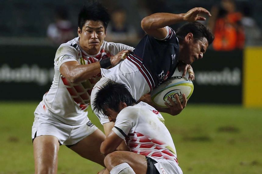 Hong Kong's Rowan Varty (centre) is tackled by Japan's Katsuyuki Sakai (below) during the men's final of the Asia Rugby Sevens qualifier, in Hong Kong on Nov 8, 2015.
