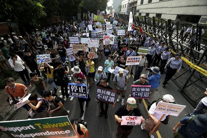 Taiwanese protesters shout slogans and hold banners during a protest against Ma Ying-jeou and Xi Jinping's meeting in Singapore, in Taipei.