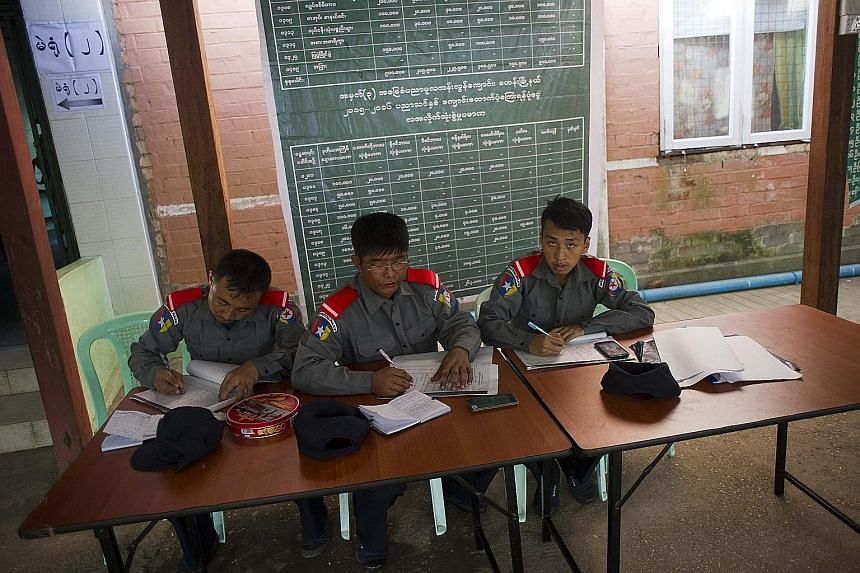 (Top) Special election police guarding a polling station where opposition leader Aung San Suu Kyi will be voting in Yangon. (Above) A man checking a voter list before advanced voting takes place at a polling station in Sittwe township of Rakhine stat