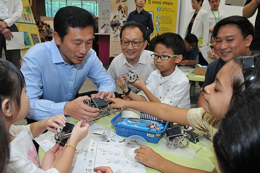 Mr Ong Ye Kung joining children in building small solar cars at the Tinkerama pop-up booth at the Lifelong Learning Festival.