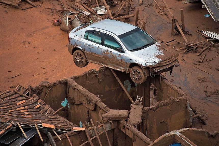 Brazilian firemen rescuing a foal near its mother in the village of Bento Rodrigues last Friday after two tailings dams burst at a nearby mine, unleashing a deluge of thick, red sludge over the village. Below: A car perched awkwardly on top of a hous