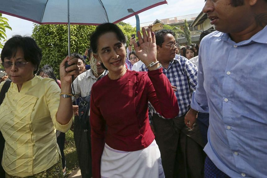 Myanmar pro-democracy leader Aung San Suu Kyi waves at supporters as she visits poling stations at her constituency Kawhmu township Nov 8, 2015.