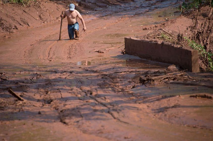 A man tries to cross a muddy area of Gesterio, part of the Barra Longo city, Brazil on Nov 07, 2015.