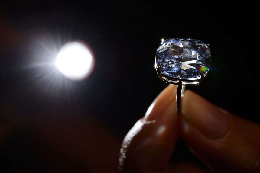 A model holds a 12.03-carat blue diamond during a press preview by auction house Sotheby's in Geneva on Nov 4, 2015.