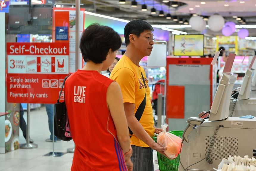 A couple using the self-checkout counter at the NTUC at Nex on Nov 8, 2015.