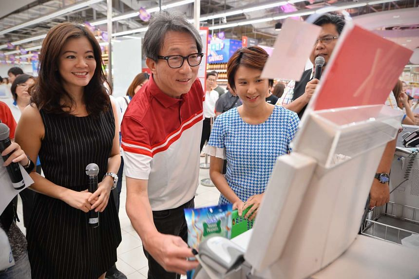 Manpower Minister Lim Swee Say (second from left) and Ministry of Trade and Industry Parliamentary Secretary Low Yen Ling (in light blue), together with celebrities Michelle Chong (left) and Suhaimi Yusof (partially hidden), using a self-checkout mac