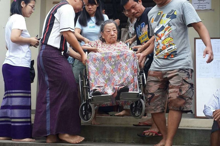 92-year-old Daw Myint Myint, in a wheelchair, being carried down the staircase after voting. Accompanying her was her daughter.