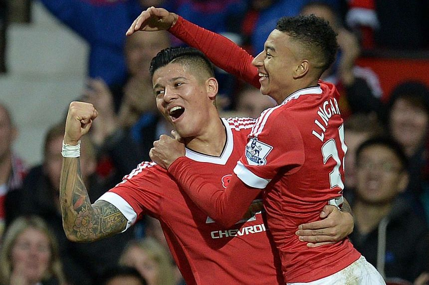 Lingard (right) celebrates scoring his team's first goal with Manchester United's Argentinian defender Marcos Rojo.