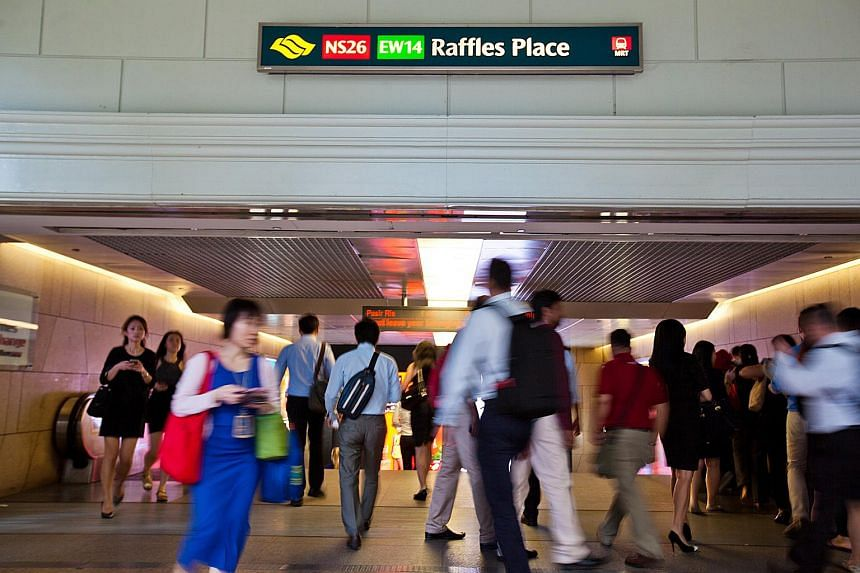Commuters at Raffles Place MRT station in the central business district of Singapore, on Oct 28, 2015.