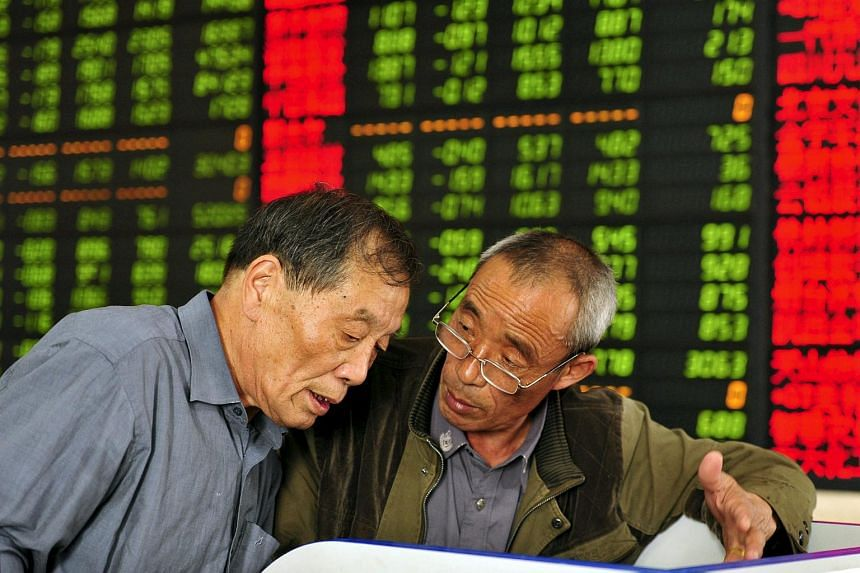 Investors talk as they look at a computer screen showing stock information at a brokerage house in China.