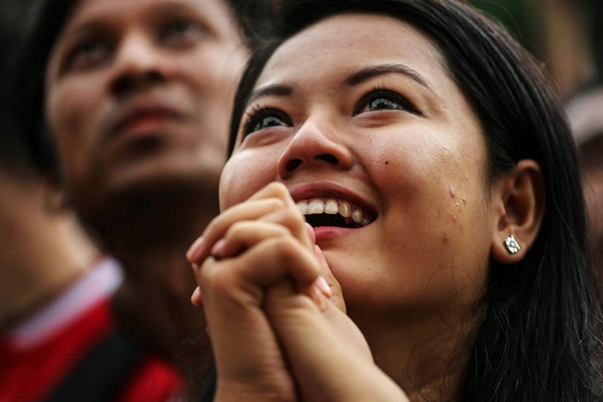 A National League for Democracy party supporter reacts as she watches a screen showing first elections results outside the party headquarters in Yangon, Myanmar, on Nov 8, 2015.