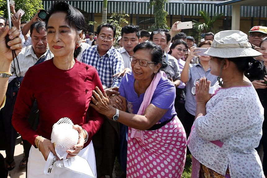 Myanmar's National League for Democracy Party's leader Aung San Suu Kyi (left) is greeted by supporters during her visit one of polling station on the way to her constituency in Kawmhu township, Yangon, Myanmar on Nov 8, 2015.