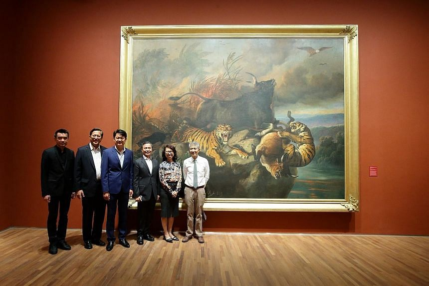 Mr Danny Yong (third from left) with board members and management of the National Gallery Singapore in front of Forest Fire by Raden Saleh Sjarif Boestaman.
