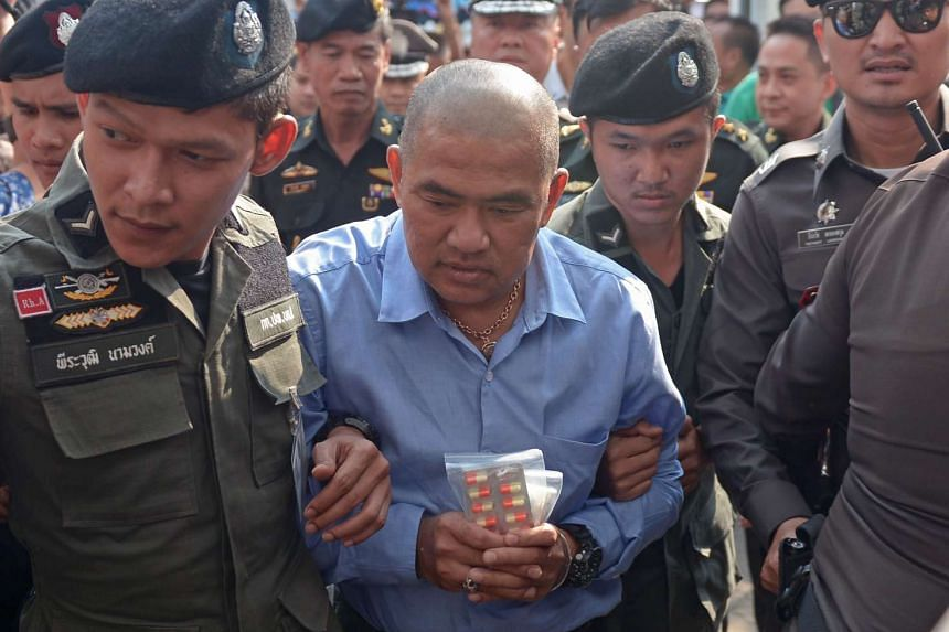 Thai fortune teller Suriyan Sucharitpolwong being escorted by police during his arrival at a military court in Bangkok on Oct 21, 2015.