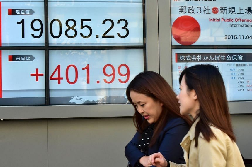Pedestrians pass before a share prices board in Tokyo, on Nov 4, 2015.