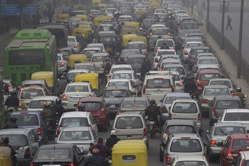 Vehicles sit in traffic on a road shrouded in haze in New Delhi, India, on Jan 20, 2014.