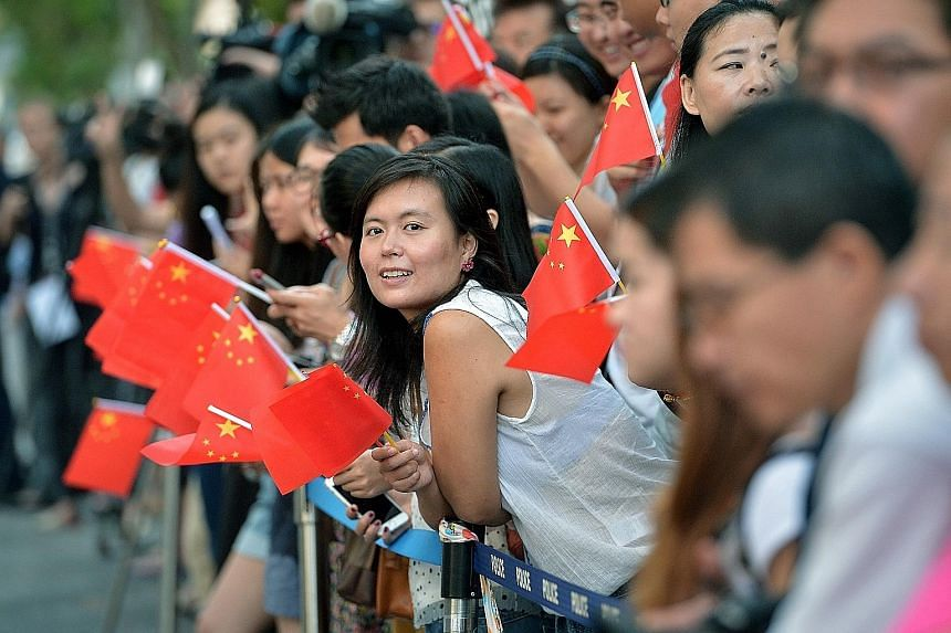 Top: People waiting to catch a glimpse of Chinese President Xi Jinping, who launched the China Cultural Centre in Queen Street last Saturday. Above: Mr Xi delivering his speech at a state banquet in the Istana.