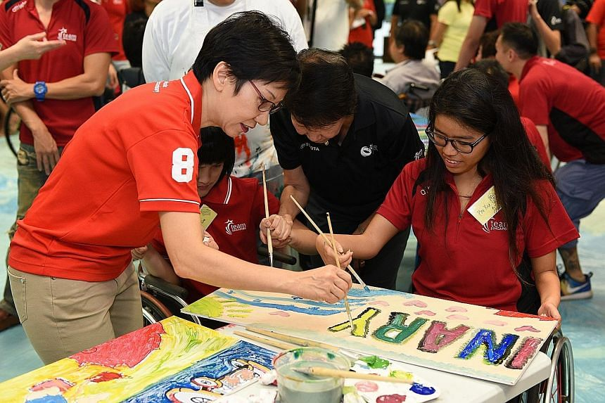 Minister for Culture, Community and Youth Grace Fu painting with para swimmer Yip Pin Xiu at a Team Singapore camp.