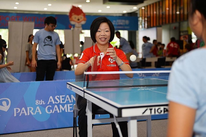 Senior Minister of State for Culture, Community and Youth Sim Ann tries her hand at table tennis at the Sport Without Boundaries Roadshow.