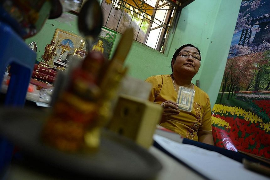 Myanmar fortune teller Hnin Ohn Mar Yee with a tarot card at her booth in the Shwedagon Pagoda compound in Yangon.