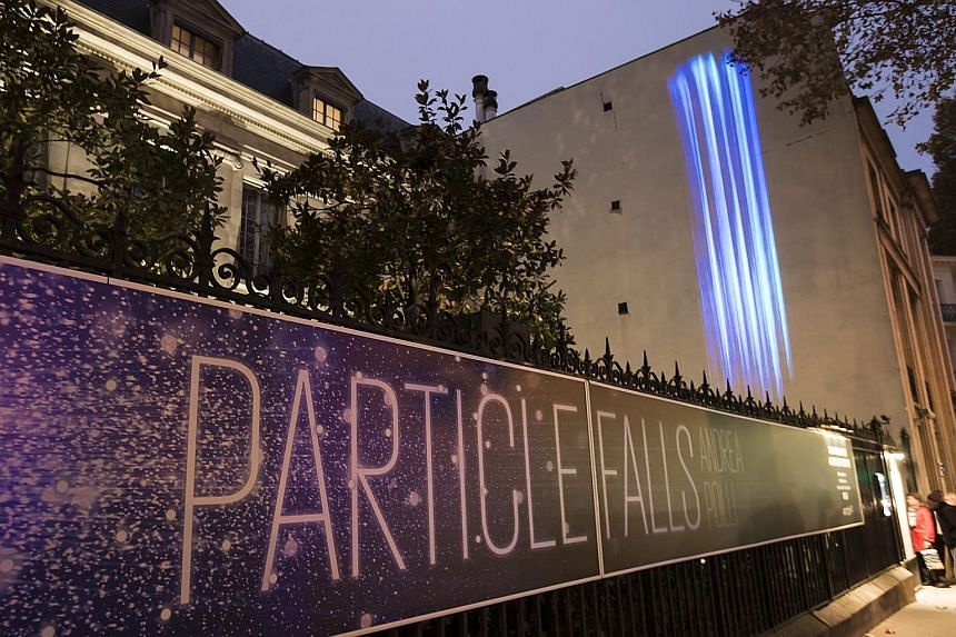 """An art installation called """"Particle Falls"""" by US environmental artist Andrea Polli projected on the Mon Bismarck American Centre in Paris, as part of an initiative to promote climate change issues."""