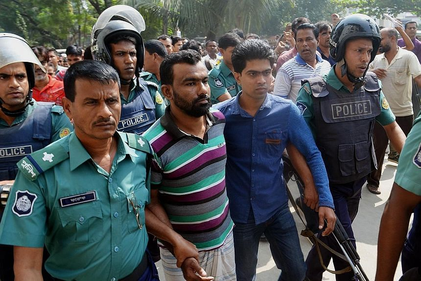 Bangladesh police escorting a suspect (centre) in the high-profile murder case involving the lynching of a 13-year-old boy at a court in Khulna yesterday.