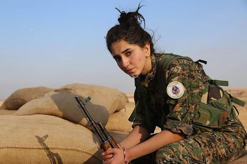 A female fighter for the Syrian Democratic Forces, which include Kurds, Arabs and Syriac Christians, guarding a post outside the town of Al-Hol in north-eastern Syria last week.