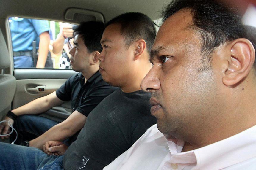 Iskandar Rahmat (centre) in a police car on July 13, 2013.