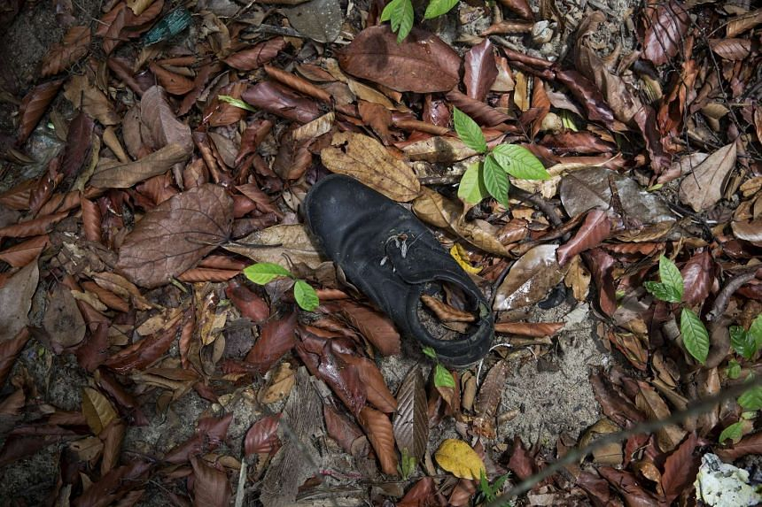 A discarded shoe is seen near an abandoned human trafficking camp in the jungle close to the Thai border in northern Malaysia, on May 26, 2015.