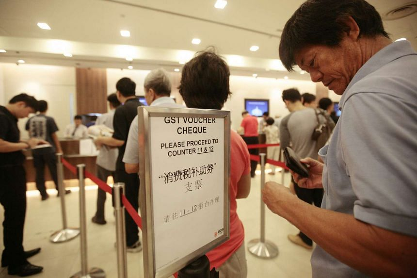 Singaporeans queueing at the UOB branch in Ang Mo Kio to encash their GST Voucher cheques on July 31, 2012.