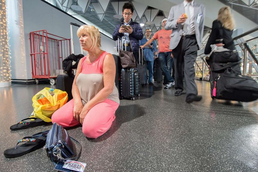 An unidentified tourist is waiting to return to Hawaii at the international airport in Frankfurt, Germany on Sunday. where housands of passengers are  stranded because of  an ongoing strike of cabin crew.