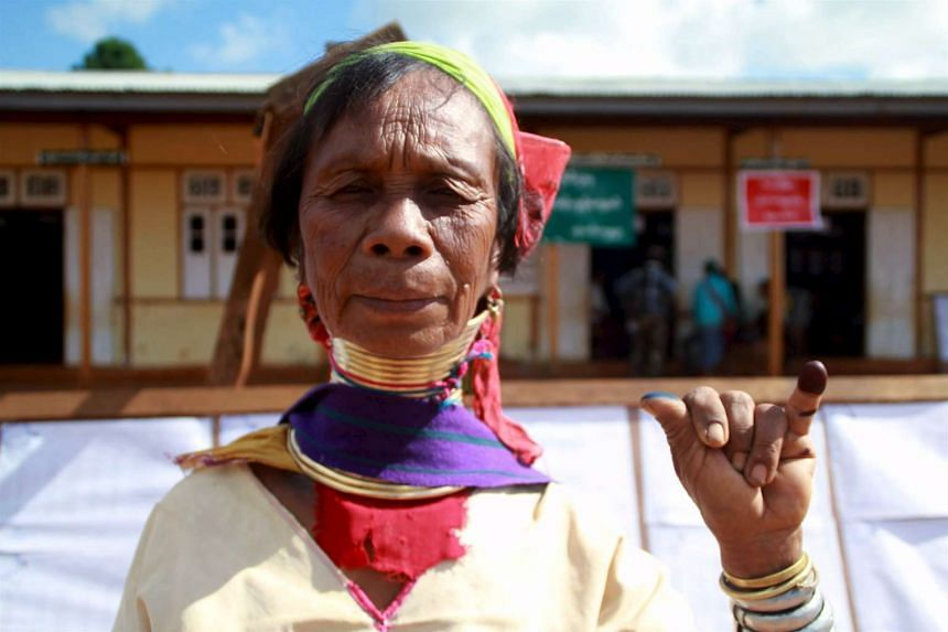 A Kayan woman, from one of Myanamr's ethnic minority groups, shows her inked finger after casting her vote, outside a polling station in Loikaw on Nov 8.