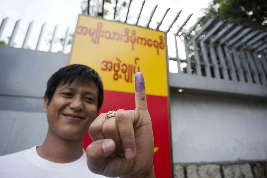 A man shows his inked finger after casting his ballot outside the residence of Myanmar opposition leader Aung San Suu Kyi in Yangon on Nov 8, 2015.