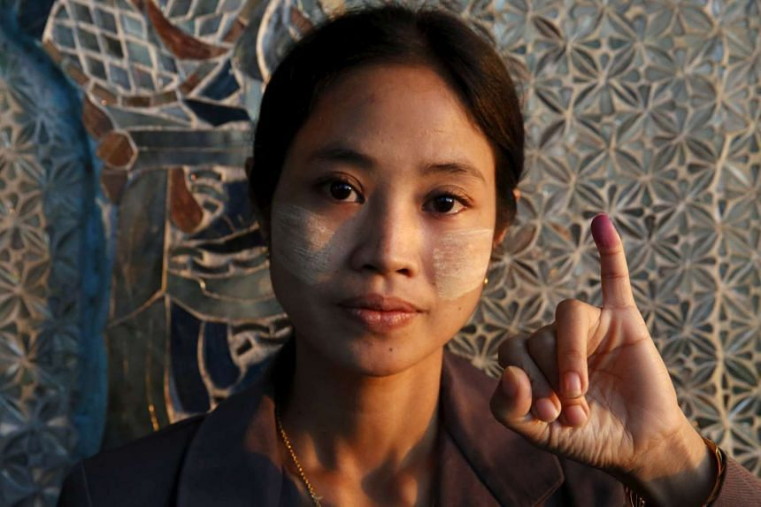 A woman shows her inked finger after voting at a Buddhist prayer hall in Mandalay on Nov 8.