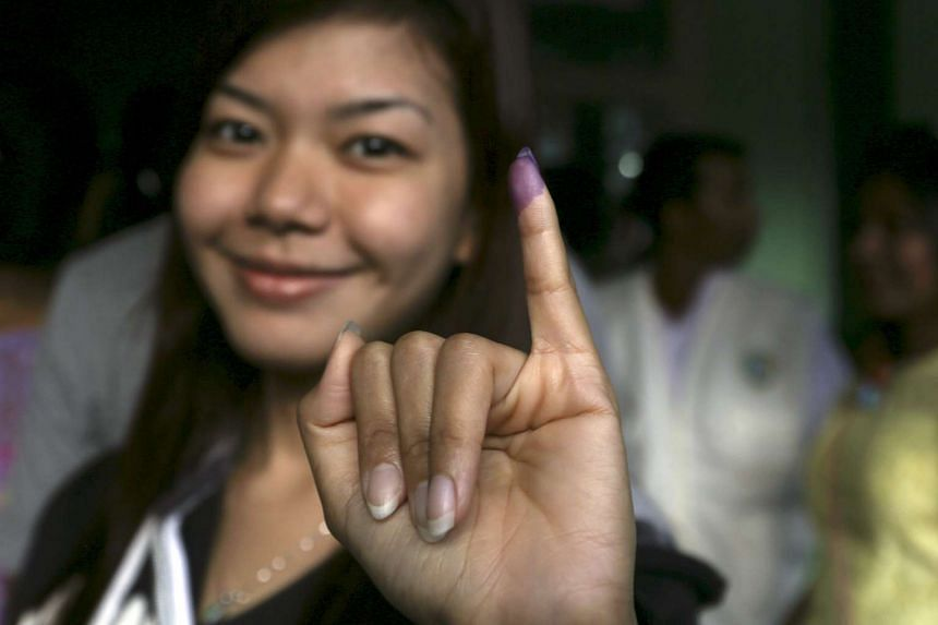 A woman shows her inked finger after casting her ballot in Yangon on Nov 8.