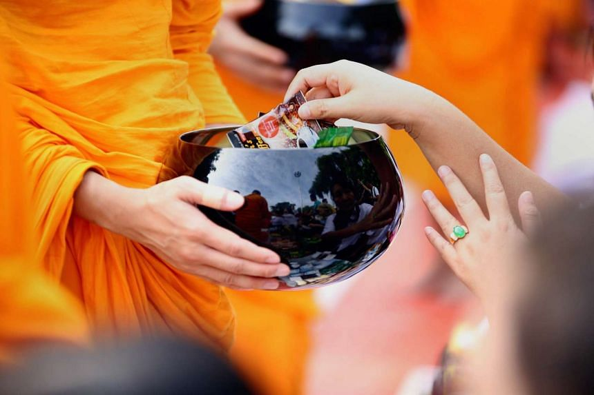 A Buddhist monk receiving morning alms in Mandalay, Myanmar, on Sept 20, 2015.