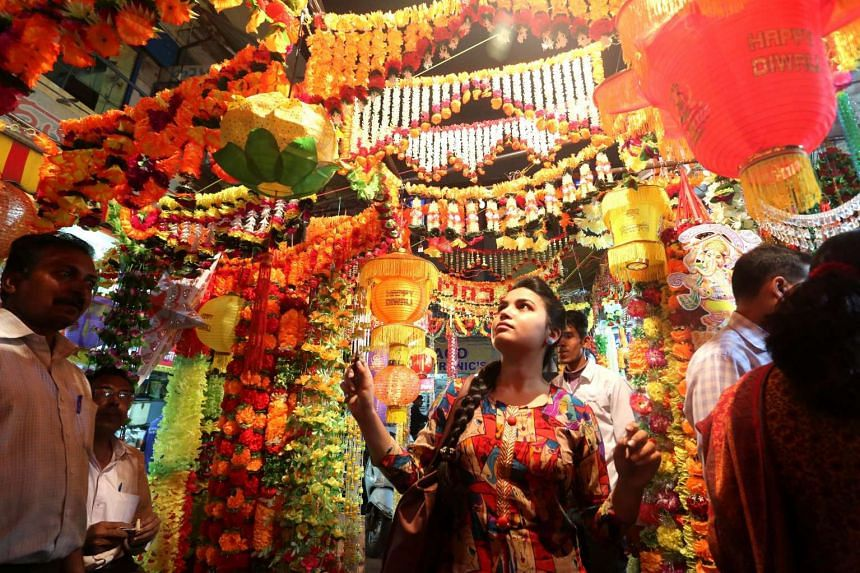 People shopping for decorative items in a market for Deepavali in Bhopal, India, on Nov 6, 2015.
