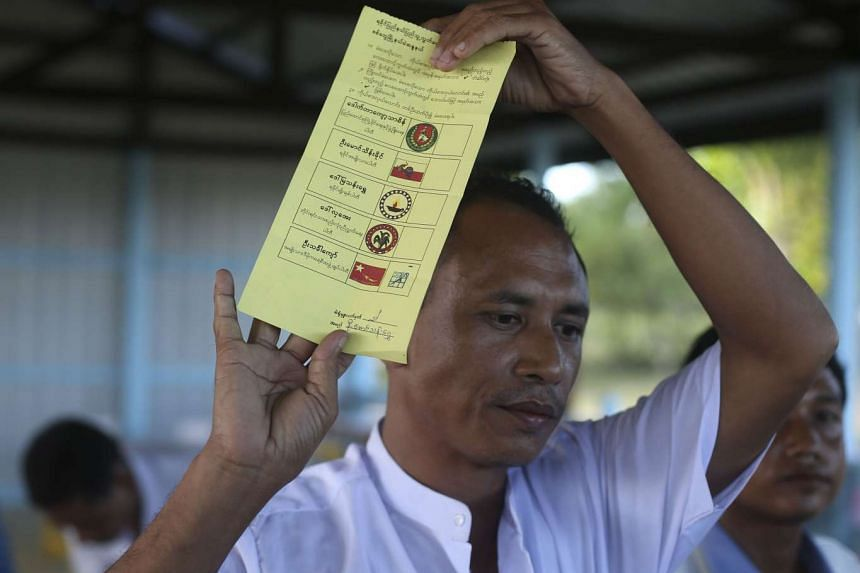 An official showing a valid vote at a polling station in Sittwe on Nov 8.