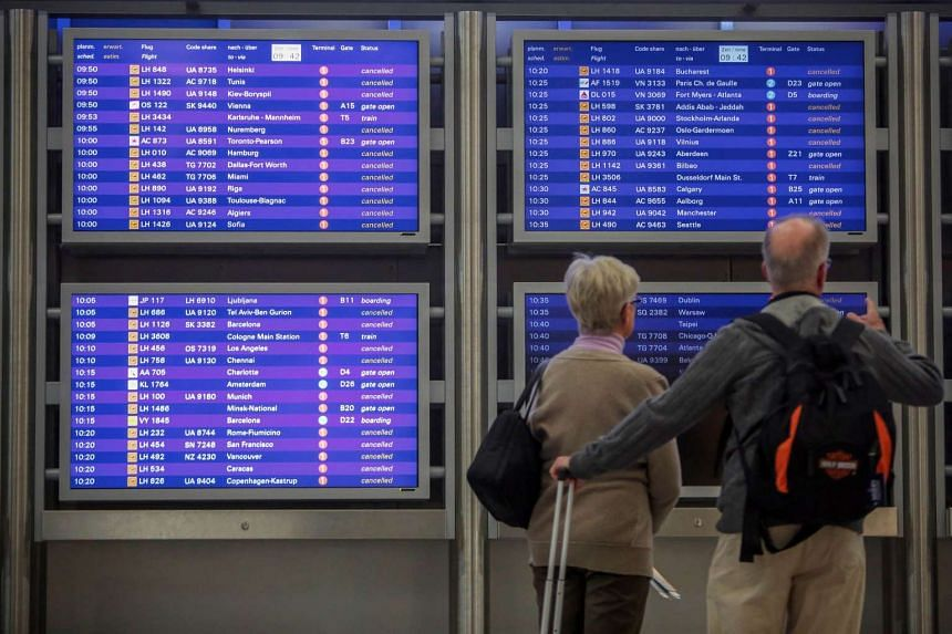 Travellers looking monitors displaying flight information, with many Lufthansa flights being cancelled, during a strike by cabin crew, on Nov 9, 2015.