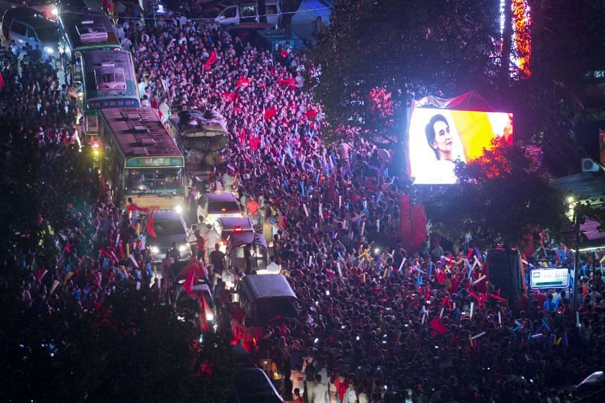 A huge crowd gathers outside the headquarters of National League of Democracy (NLD) party displaying a huge portrait of Myanmar opposition leader Aung San Suu Kyi.