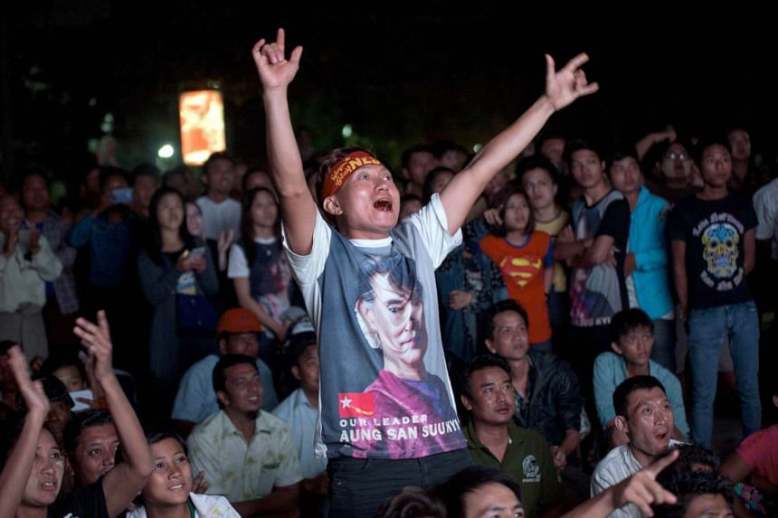 An NLD supporter cheering the election results outside the party's office in Mandalay on Nov 9.