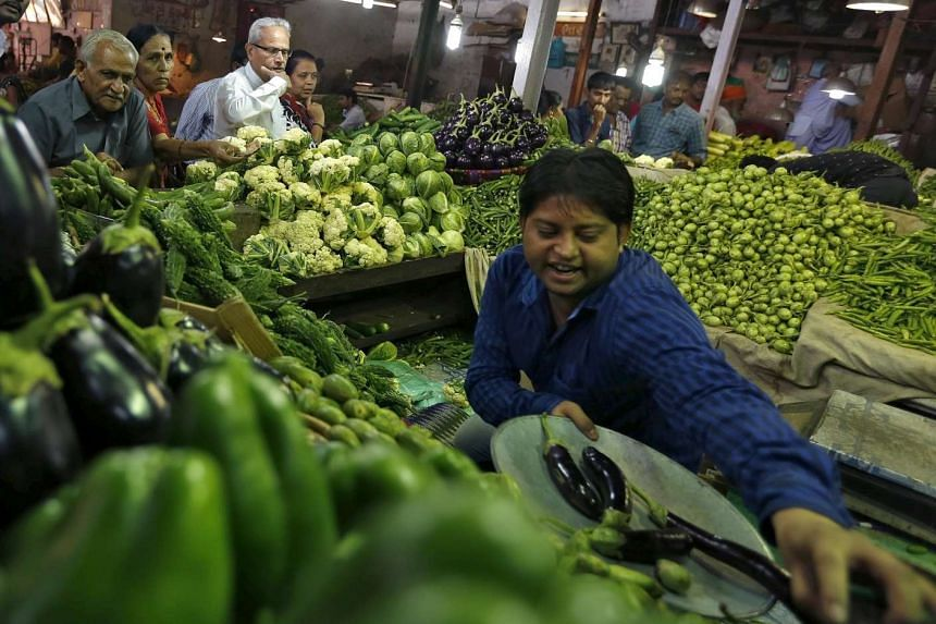 Customers buy vegetables at a market in Ahmedabad, India.