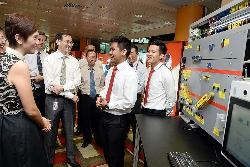 Mrs Josephine Teo talking to Singapore Polytechnic students Amirul Husni Sidek (third from right) and Bryan Lim Wen Chong (far right), both 19, during a tour of the school's rapid transport technology programme exhibition. With them is SMRT group chi