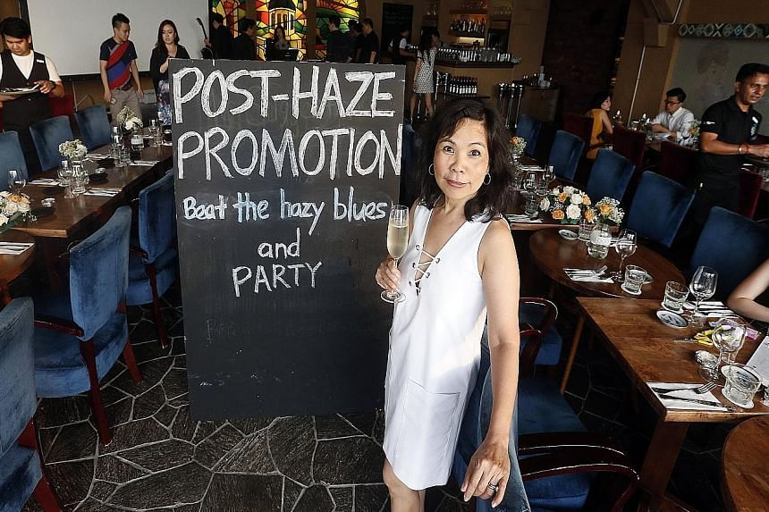 Ms Belinda Lim, co-owner of The Wine Company, says the restaurant is waiving the $8,000 minimum spend to hold functions at its three outlets as it tries to earn back what it lost from cancellations during the haze.