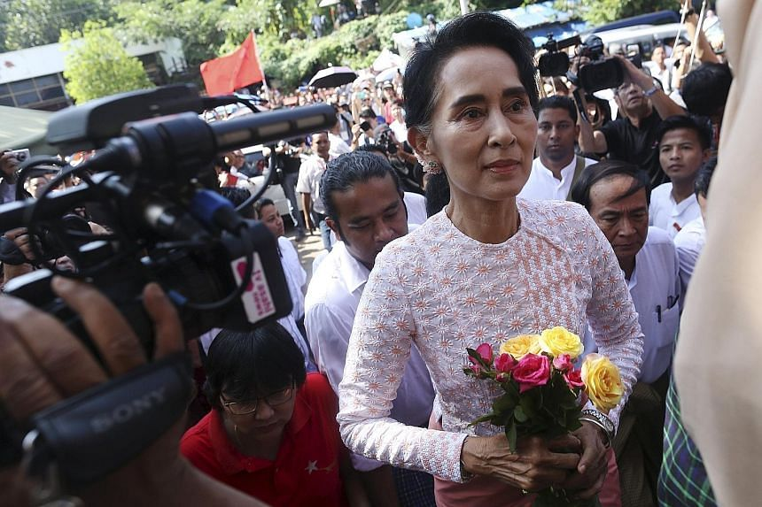 Ms Aung San Suu Kyi arriving at the NLD headquarters in Yangon yesterday, where supporters were celebrating in expectation of a big win.