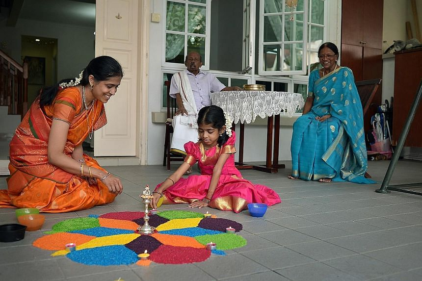 Madam Jayapaul Eswari and her daughter Shree Nethi working on a multi-coloured rangoli floor decoration at the driveway of their Lentor Crescent home yesterday. Behind them are Shree Nethi's grandfather M.K. Narayanan and grandmother Sarasvathi Kasiv