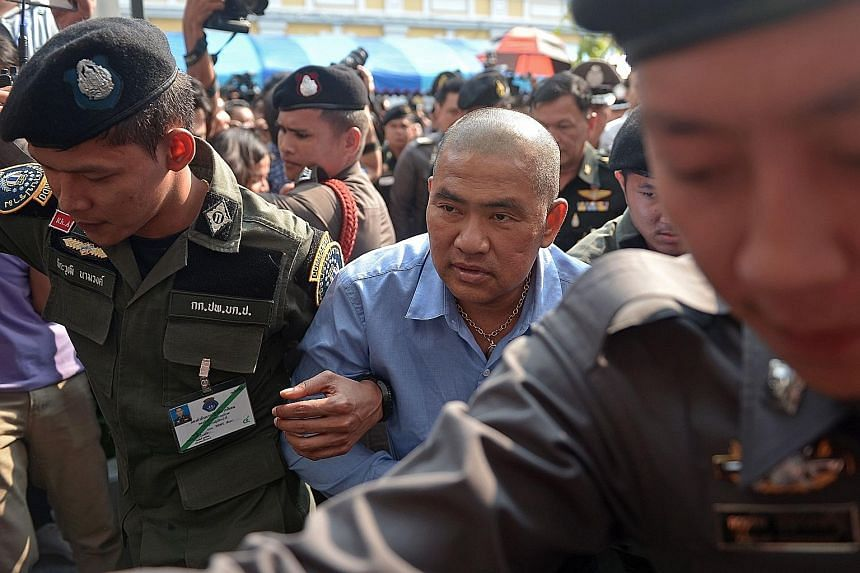An Oct 21 file photo of Thai fortune teller Suriyan Sucharitpholwong (in blue), 54, also known as Mor Yong, arriving at a military court in Bangkok. The fortune teller, who was charged with royal defamation, died in military custody, officials said y